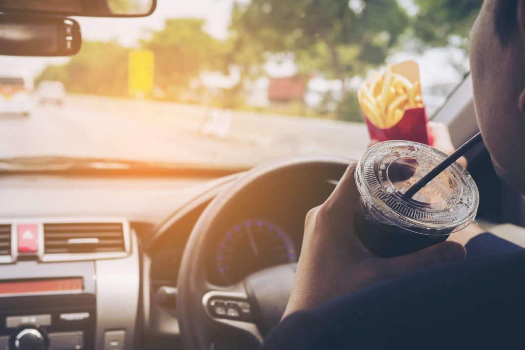 Man driving car while eating French fries and soft drink, left-driving countries